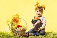 Easter little girl, kid bunny rabbit, basket eggs. Easter little girl, kid holding bunny rabbit basket eggs over yellow background Royalty Free Stock Images