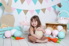 Easter! Little girl in overalls sits with a large Easter egg. Easter location, decorations. Family holidays, traditions. Colorful stock image
