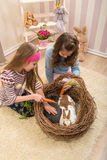 Easter - Little girls stroking the rabbits, the nest Royalty Free Stock Images