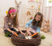 Easter - Little girls stroking the rabbits, the nest Stock Photography