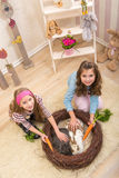 Easter - Little girls stroking the rabbits, the nest Stock Image