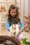 Easter - Little girls stroking the rabbits, the nest Royalty Free Stock Photo