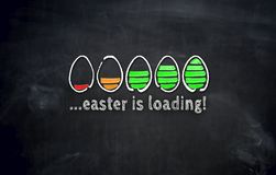 Easter is loading concept with eggs on blackboard