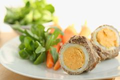 Easter lunch or dinner. Recipe idea, cooked egg in a roll of veal meat, served with cooked carrots, potato and fresh corn salad royalty free stock images
