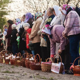 At Easter many people standing in a row with baskets and candles, waiting for the priest to bless. Ukraina.Fastov. May 1, 2016 Stock Photo