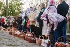 At Easter many people standing in a row with baskets and candles Royalty Free Stock Images