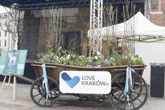 2018 Easter Market, Krakow, Poland, Europe. KRAKOW, POLAND - MARCH 23, 2018: An old cart on wheels filled with Easter flowers and willows in front of staging royalty free stock photography