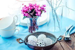 Easter. Modern painted easter eggs and spring violets on wooden table Royalty Free Stock Images