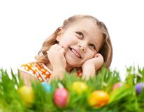 Easter mood. Photo of cute girl lying in green grass with colorful Easter eggs in it royalty free stock photography