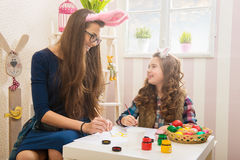 Easter - Mother and daughter paint eggs, bunny ears on them Stock Photography