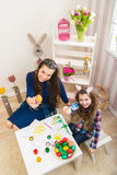 Easter - Mother and daughter paint eggs, bunny ears on them Royalty Free Stock Photos