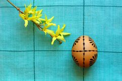 Easter motive. Geometrical easter motive with one traditionally decorated egg and a little branch of forsythia Stock Photography