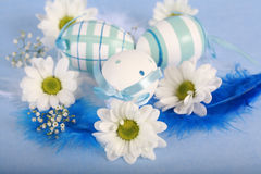Easter motive. Photo of Easter eggs and flowers on blue background Royalty Free Stock Photo