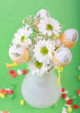 Easter motive. Photo of Easter eggs and flowers on green background Stock Photography