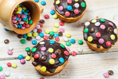 Easter muffins with chocolate glaze and candies Stock Photos