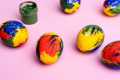 Easter multi-colored eggs, paints and brush on a table. Preparation for a holiday stock photos