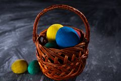 Easter multicolored eggs in a basket on a dark blurred background royalty free stock photo