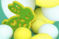 Easter multicolored eggs and a yellow-green toy rabbit made of felt. Easter multicolored eggs and yellow-green toy rabbit made of felt Stock Images