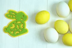 Easter multicolored eggs and a yellow-green toy rabbit made of felt, happy Easter. Easter multicolored eggs and a yellow-green toy rabbit made of felt Stock Images
