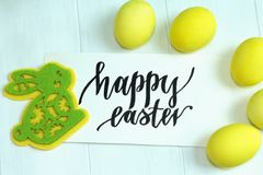 Easter multicolored eggs and a yellow-green toy rabbit made of felt, happy Easter. Easter multicolored eggs and a yellow-green toy rabbit made of felt Royalty Free Stock Photography