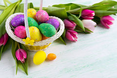 Easter multicolored glitter eggs in yellow basket and red tulips Stock Photography