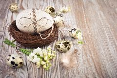 Bird`s nest, eggs and lily of the valley on wood. Easter natural decorations - bird`s nest, eggs and lily of the valley on wooden table Stock Images