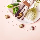 Easter natural table setting decorated with quail eggs and green sprigs. Beautiful arrangement.  stock photography