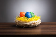Easter nest with colored eggs on table, gray background Stock Images