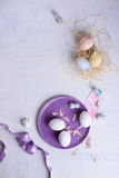 Easter nest with colored eggs on white background. Pastel decoration for spring holiday. Above view, copy space. Stock Image