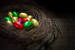 Easter nest with colorful wrapped chocolate eggs on a rustic woo Stock Images