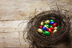 easter nest with colorful wrapped chocolate eggs on rustik wooden planks, copy space royalty free stock image