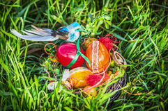 Easter nest with decorating eggs and blue bird in garden grass Stock Image
