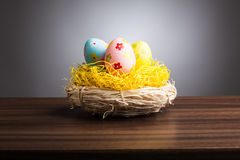 Easter nest with decoration eggs on table, gray background Royalty Free Stock Images