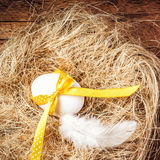 Easter nest with Egg, yellow ribbon and white feather on wooden Stock Photo
