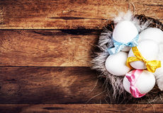 Easter nest with Eggs,  ribbons and white feathers Stock Image