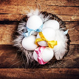 Easter nest with Eggs,  ribbons and white feathers on wooden bac Stock Photo