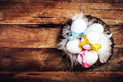 Easter nest with Eggs,  ribbons and white feathers on wooden bac Stock Photos