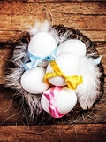 Easter nest with Eggs,  ribbons and white feathers on wooden bac Royalty Free Stock Photos