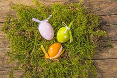 Easter nest with painted eggs. On a wooden plank Stock Photo