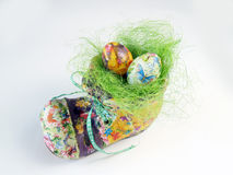 Easter nest in the shoe. Colorful Easter eggs and garden shoe at the white background royalty free stock images