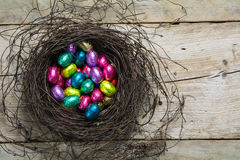 Easter nest with wrapped chocolate eggs in pastel colors on rust Stock Photography