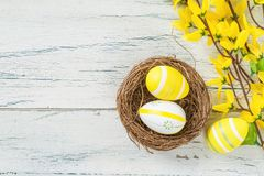 Easter nest with yellow easter eggs on a wooden background Stock Photo