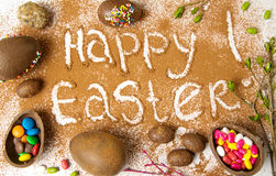Easter note in cacao powder with chocolate eggs stock photos