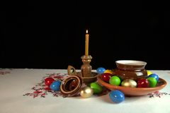 Easter. Orthodox Easter. On the table is a plate with colored eggs. Nearby stands a candle in a candlestick. Black background. Under the alpha channel Stock Images