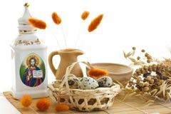 Easter. Ovos de codorniz na cesta, no prado e no carafe Imagem de Stock