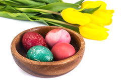 Easter painted eggs and bunch of tulips on a white. Background Stock Images