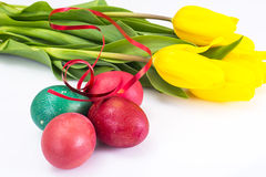 Easter painted eggs and bunch of tulips on a white Royalty Free Stock Photography