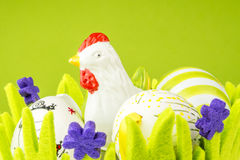 Easter painted eggs and cock in green basket made of fabric Royalty Free Stock Photos