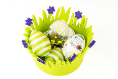 Easter painted eggs in green basket made of fabric Stock Images