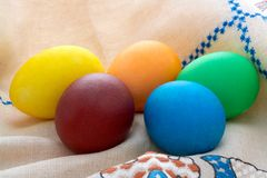 Easter  painted eggs on unbleached linen with embr Royalty Free Stock Image